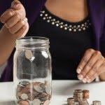 lady placing coins inside jar