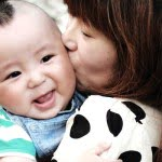 Cute baby boy getting kissed by mom