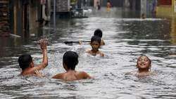 image of kids swimming in floodwater