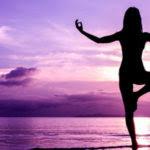 Lady doing yoga on the beach