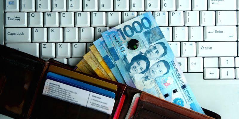 Pesos in Cash Inside Wallet on top of keyboard