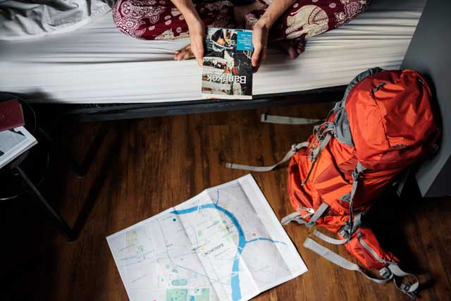 Backpacker In Hostel With Bangkok Guide and Map