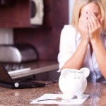 Lady covering face with white piggy bank