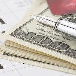 Pen on top of $100 bills and calendar